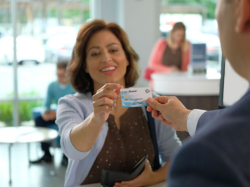 Smiling woman receiving debit card from banker